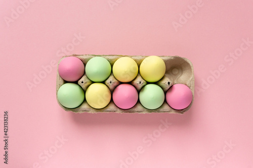 Obraz Easter eggs painted in pastel colors in cardboard box on pink background, top view - fototapety do salonu