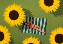 Woman In Bikini Sunbathing On Blanket Among Large Sunflowers