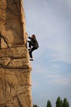 Businessman Climbing Steep Rock Face