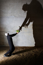 Man Offering Flowers To Tall Ominous Shadow On Wall