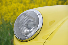 Close-up Of A Headlight Of A Yellow Vintage Oldtimer Car In Field Of Rapeseed