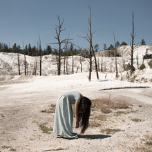 Conceptual Fine Art Portrait Of A Girl In Blue Dress Standing Near Burned Trees On Salt Plane In Yellowstone National Park