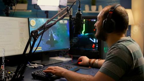 Fotografie, Obraz Streamer man wearing headset start to play online space shooter video games