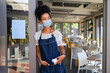 canvas print picture African waitress standing at entrance with face mask during covid