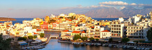 Greece. Crete. Panorama Of The Beautiful Southern Town Of Agios Nikolaos From The Top Observation Deck In The Setting Sun. Tourists On The Embankment Are Out Of Focus