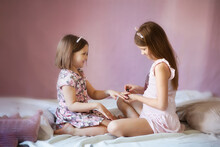 Cute Funny Kids Girl Sisters Paint Nails With Nail Polish On A Pink Background, Gentle Feminine Photo, Soft Focus. Concept Childhood And Sisters Girlfriend, Beauty Lessons