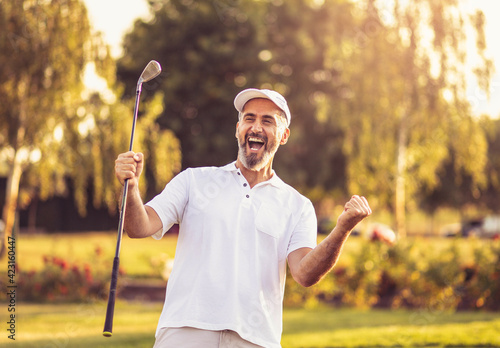 Fototapeta Happy successful man on golf field.