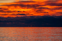 Glorious Sunset Over The Sea With Dark Clouds On The Horizon And Red Reflections On The Rippling Water
