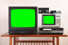 Two Antiquated Vintage TVs With VCRs With Blank Green Screens Sit On A Vintage Table In A 1990s Tenement Building.