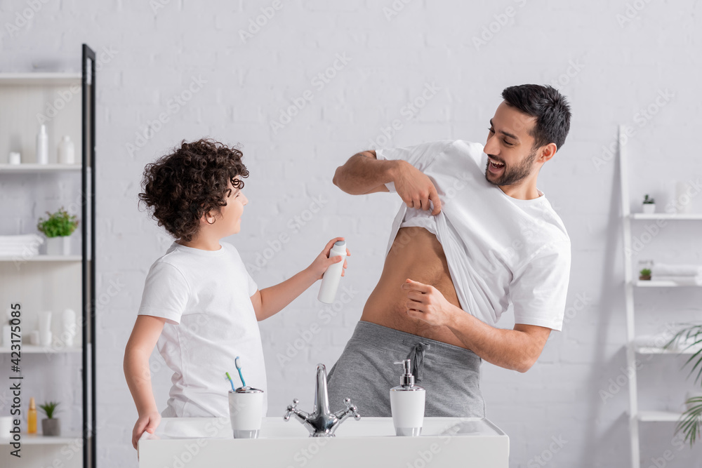 Fototapeta Cheerful arabian man lifting t-shirt near son with deodorant
