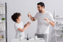 Angry Muslim Man Holding Deodorant Near Son With Sprayer
