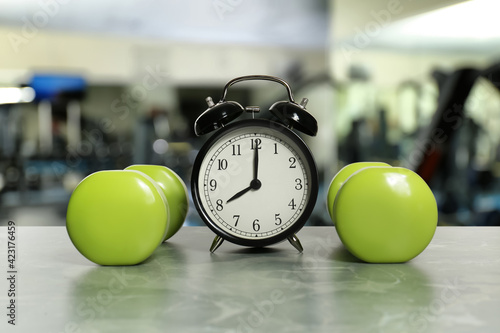 Alarm clock and dumbbells on marble surface in gym. Morning exercise