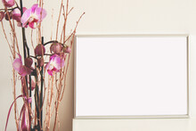 Silver Horizontal Empty Frame On White Table With Pink Orchid Flowers, Mockup For Arts, Photos Illustrations