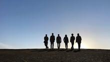 男女6人のシルエットと夕暮れの空