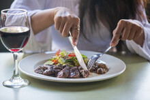 Close Up Of Woman Eating Steak And Drinking Red Wine In A Restaurant Or Cafe