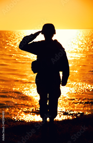Fotografie, Tablou Silhouette of army soldier, Marines fighter in helmet and ammunition saluting while standing on seashore at sunset time