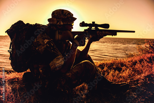 Commando team sniper, army special forces shooter aiming, shooting sniper rifle while sitting on sea or ocean shore during sunset Fototapeta