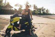 Stylish Barefooted Guy Using Smartphone Sitting On Motorbike In Tropical Resort
