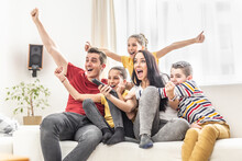 Enthusiastic Family Of Five Cheers At Home Watching Sports On TV