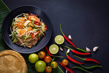 Papaya Salad, Thai Food Cooked With Papaya, Tomato, Green Beans And Peanuts Placed On A Black Table.