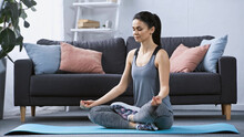 Young Woman In Sportswear Meditating On Fitness Mat At Home