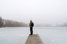 Man Standing On A Bridge In The Fog