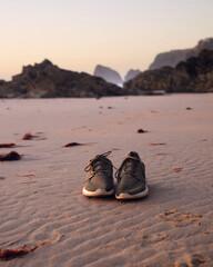 buty pozostawione na dzikiej plaży o zachodzie słońca