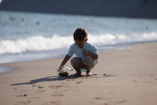 The Boy In The Summer Sat Down And Plays On The Beach Near The Sea With A Toy Boat, Which Is In A Bottle