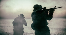 Commando Soldiers Walking In Water, Army Special Operations Forces Fighters Sneaking In Darkness, Aiming Assault Rifles And Observing Shore During Amphibious Operation On Coast At Night Or Dawn