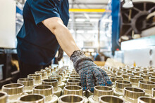 Male Worker Checks Many Metal Pipe Couplings In A Pipe Factory