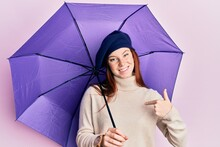 Young Red Head Girl Holding Purple Umbrella Wearing Fresh Beret Pointing Finger To One Self Smiling Happy And Proud