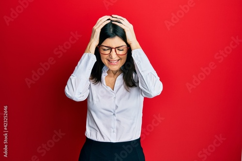 Young hispanic woman wearing business shirt and glasses suffering from headache desperate and stressed because pain and migraine. hands on head.