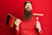 Redhead Man With Long Beard Holding Fork With Pork Sausage And Germany Flag Looking At The Camera Blowing A Kiss Being Lovely And Sexy. Love Expression.