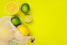 Bright Summer Citrus Flatlay With Lemons And Limes In The String Mesh Bag Isolated On Yellow Background.