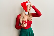 Beautiful Caucasian Woman Wearing Christmas Costume And Hat Surprised With Hand On Head For Mistake, Remember Error. Forgot, Bad Memory Concept.