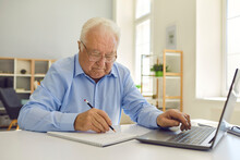 Senior Man In Eyeglasses Sitting At Desk At Home, Using Laptop And Taking Notes In Notebook