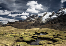 Mountain Peaks And What Looks Like Giant Moss Covered Toad Stools In A Surreal Looking Landscape Located In The Cordillera Huayhuash In The Andes Mountains Of Peru.