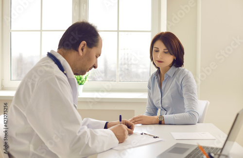 Canvas-taulu Middle-aged woman patient looking at doctor writing prescription or examination notes at worktable