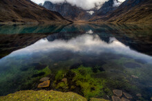 A Polarizing Filter Shows Rocks And Green Grass In Lake Carhuacocha During A Reflection And Sunrise In The Cordillera Huayhuash Of The Andes Mountains In Peru.