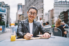 Portrait Of Cheerful Japanese Woman Sitting In Street Cafe And Smiling At Camera During Time For Studying, Happy Hipster Girl In Otpical Eyewear For Vision Correction Preparing To School Exams