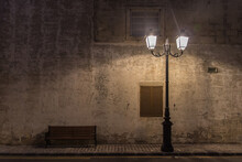 Historical Ancient Street Lamp And A Bench At Night With The Wall With Old Windows Shutters Behind Them And The Old Stony Pavement On The Road With Yellow Lines