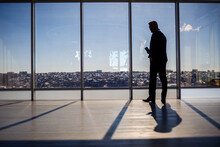 Rear View Of A Businessman Looking Out Of A Large Window Overlooking The City. He Has A Phone In His Hands. Horizontal View.