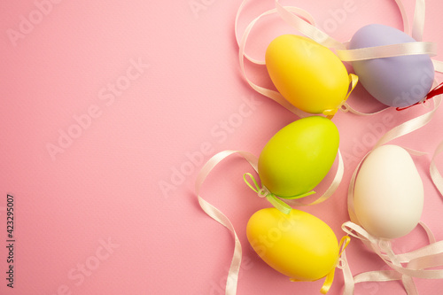 Obraz Colored eggs on a pink background with satin ribbon. Easter celebration concept - fototapety do salonu