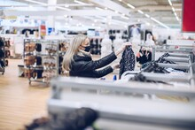 Blonde Woman Wearing Protective Face Mask Shopping Fashion Cloths In Department Store.