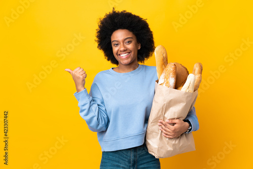 Photo Young African American woman buying something bread isolated on yellow backgroun