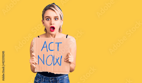 Fototapeta Young beautiful blonde woman holding act now banner scared and amazed with open mouth for surprise, disbelief face obraz