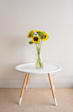 Vertical View Of Sunflowers In Glass Vase On Small Round Table Against White Wall (selective Focus)