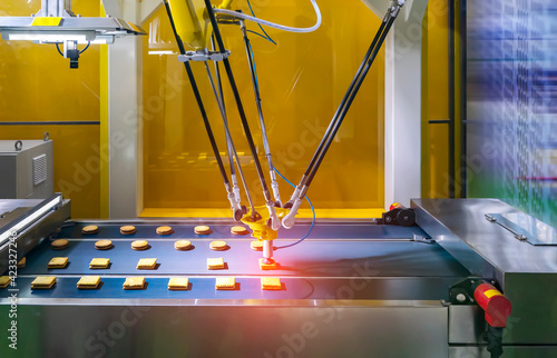 Obraz automate robot with vacuum suckers with conveyor in Production of biscuits in a manufacture factory for the food industry - fototapety do salonu