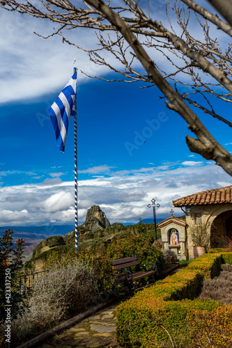 Monastery garden view with the Greek flag, patio and place for worship with icon, well maintained plants and typical church architecture. Meteora, Greece, sunny early spring day landscape Wall mural