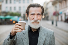 Portrait Of Happy Man With Grey Beard And Hair Enjoying Fresh Coffee-to-go Outdoors. Mature Male In Grey Jacket And Black Shirt Smiling And Looking At Camera. Blur Background Of Big City Street.